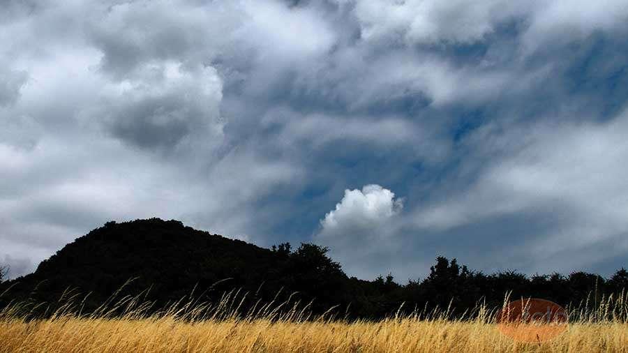 """A horizont jelentősége a tájképben: A kékes összhatású, érdekes felhőrajzú kép felső része erőteljesebb. Ezt lehetett tovább növelni a 16:9 oldalarányú vágással a sárgás előtér rovására. A vékony felület így nem kiegyenlíti, hanem erősíti az ég hatását. A két kiugró fa, és a közöttük húzódó mélyedés törést visz a két réteget elválasztó hegyvonulatba, ezzel tartva egyensúlyban a képet, hiszen a szemünk is ezen a ponton talál """"megnyugvást"""". Ebben nagyban segít a felette lévő, szinte világító felhő."""