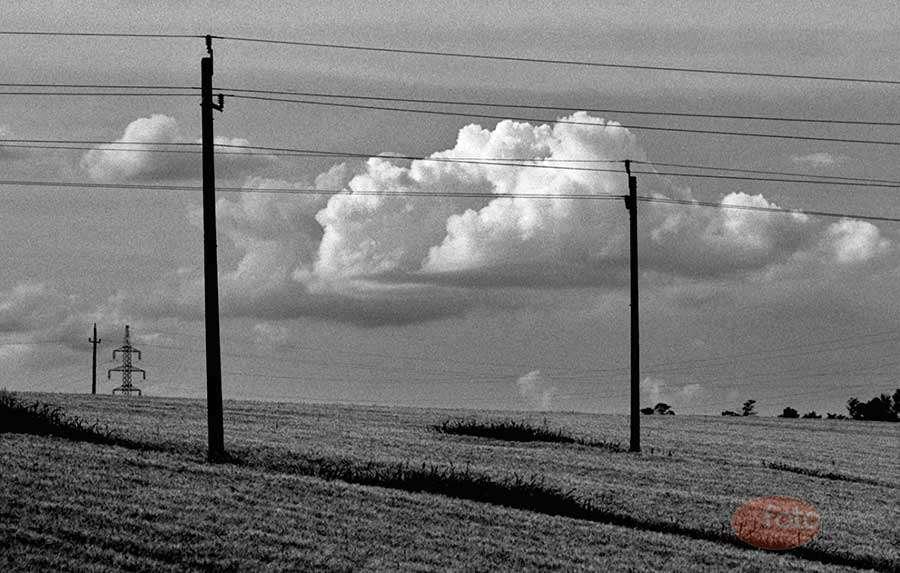 A horizont jelentősége a tájképben: Ezen a képen látszatra semmi sem egyenes. Csak a horizont mögül előbukkanó, függőleges középvonalú traverz ad támpontot a szemnek. A drótoktól összekuszált kép nyugtalanságát a szelíd felhőzet ellensúlyozza.