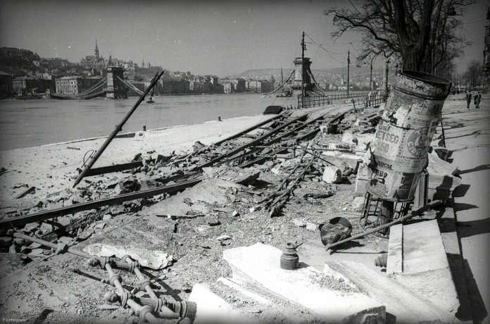 Dunakorzó, Duna-part, a felrobbantott Lánchíddal. A háború után is csinált egy korszakos képet: a győztes Sztálin csokrot kap a Dinamo stadionban. Csak egyet kattinthatott a kazettás géppel. Haldejt a szívbaj kerülgette, hogy elkapta-e a pillanatot. Annyira el, hogy az emberarcú és győzedelmes Sztálin – mellette a másik gyermeket felemelő Molotov külügyminiszterrel – ismét az új korszakába lépő Szovjetunió szimbóluma lett. A gép mellesleg egy amerikai Speed Graphic volt, amit Haldej még Berlinben kapott egy bizonyos Robert Capától. (Fotó: Vörös Hadsereg / FORTEPAN)