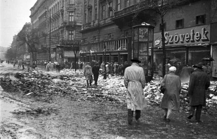 A Lenin (ma Teréz) körút az Oktogon felől a Szófia (ma Dohnányi) utca felől nézve 1956-ban Útközben, a Nagykörút és a Szófia utca sarkán egy könyvégetéshez kiérkező ÁVO-s csapat eltévedt golyója eltalálta, és a sérülésbe belehalt. Először egy közeli, Izabella utcai bérház udvarán temették el. (Fotó: Pesti Srác / FORTEPAN)